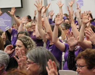 Supporters of American Sign Language interpreters in Eugene Chapter 1 raise their hands to show applause at a Eugene School Board meeting.